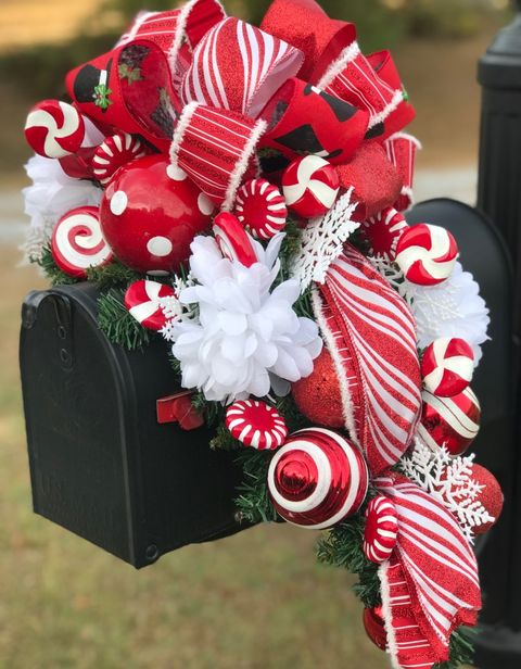 black mailbox with red and white dotted and striped christmas balls, ribbon, and decorative candies with white flowers