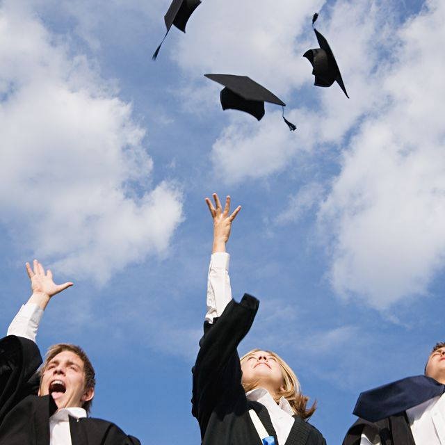 One boy and two girls celebrating graduating, throwing their caps in the air