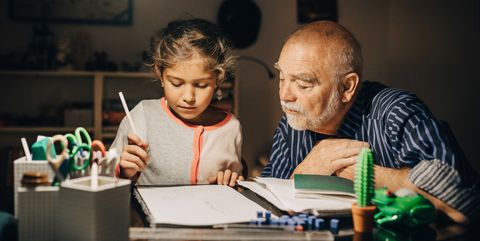Grandfather looking at granddaughter writing homework on desk in house