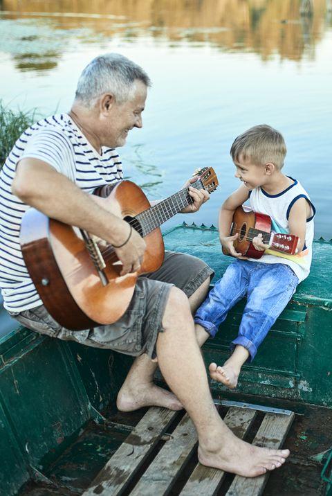grandfather teaching grandson playing guitar