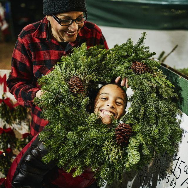 grandmother holding christmas wreath around smiling grandson