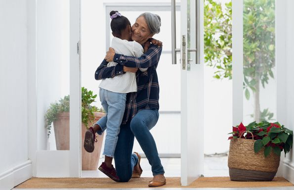 front view of grandmother hugging her granddaughter authentic senior retired life concept