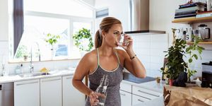 Vrouw drinkt water in sport outfit