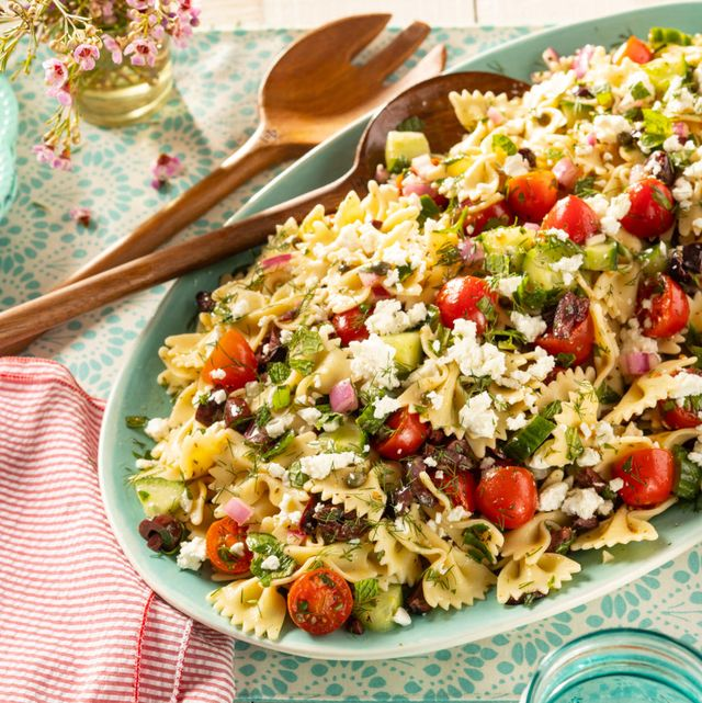 greek pasta salad with wooded serving spoons