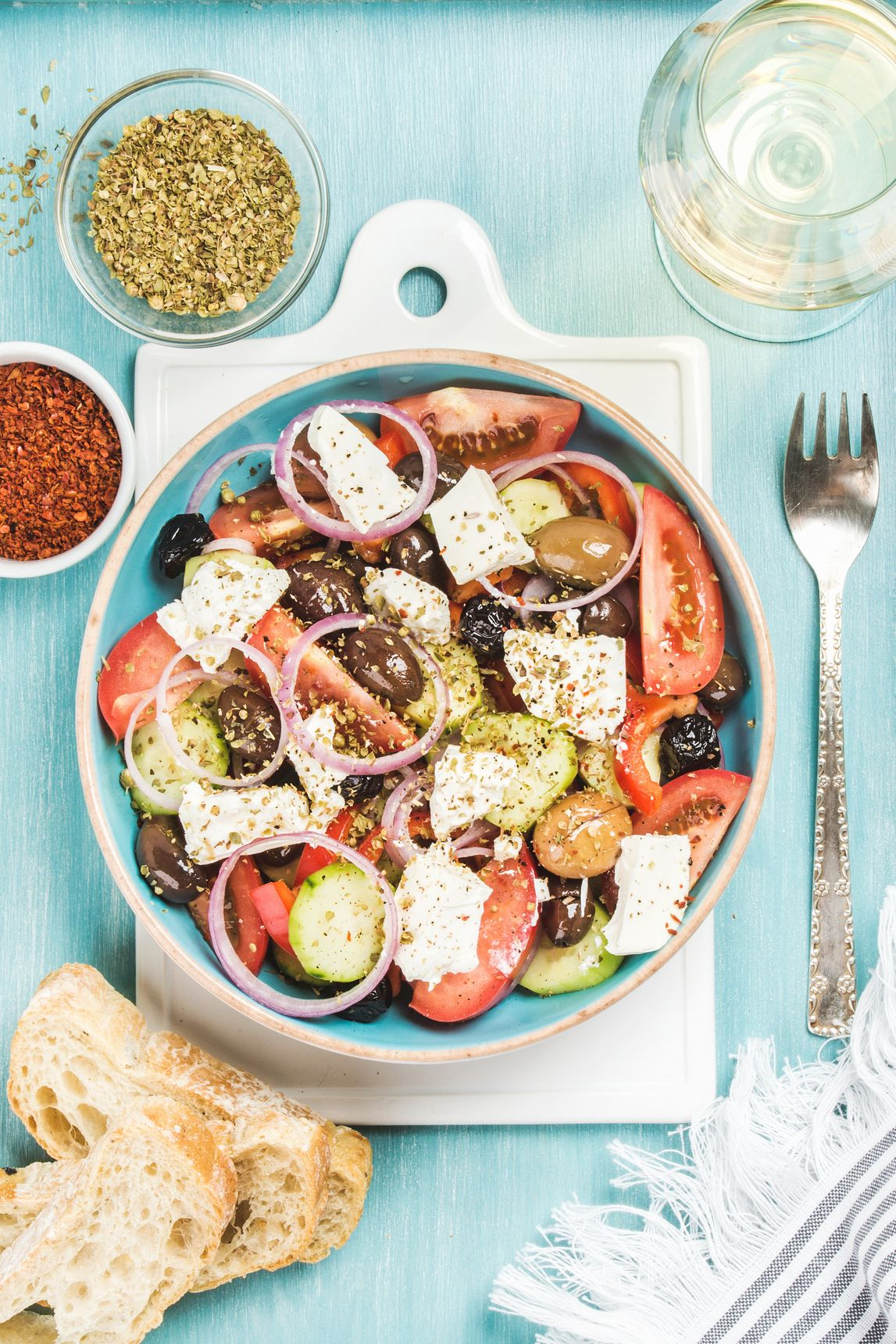 Greek salad with bread, oregano, pepper and glass of wine