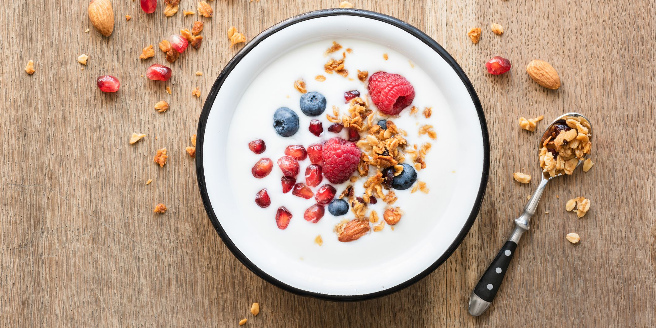 Greek yogurt with granola and berries on wooden table