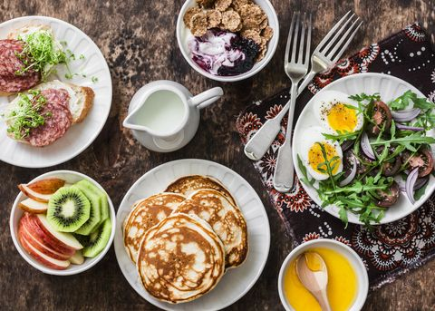Greek yogurt with whole grain cereals and berry sauce, pancakes, arugula, cherry tomatoes, boiled eggs salad, kiwi, apples fruit, salami and cream cheese sandwiches on a wooden background, top view. Flat lay breakfast table