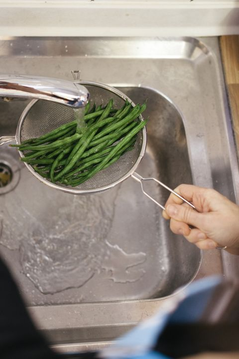 green beans being washed in kitchen sink