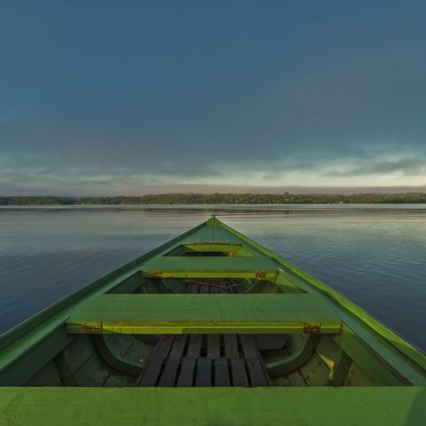 Green boat crossing the Rio Negro river at sunrise in the Amazon region, Anavilhanas Natural Reserve, Amazonas, Brazil