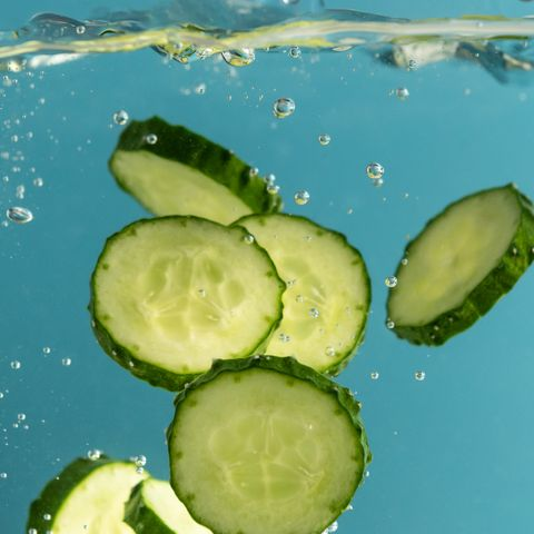 green cucumber slices in water with splash, blue background