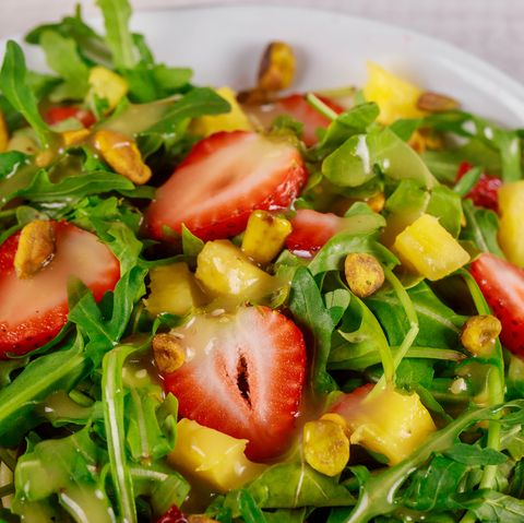 Green fresh salad with arugula, strawberries, mango and pistachios. Close up.