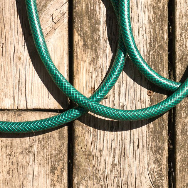 colour close up of green hosepipe coils on wooden decking, shot from above