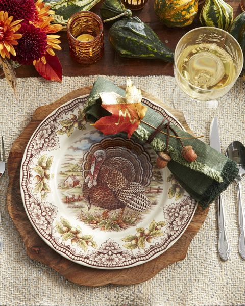 preserved leaf place card with golf leaf and acorn and string napkin ring on a thanksgiving table