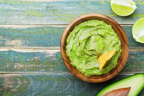 green guacamole with  ingredients avocado, lime and nachos on wooden vintage table top view