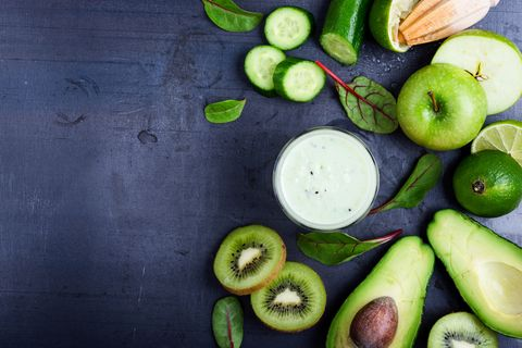 Green smoothie with fruit and vegetable ingredients on grey rustic table with copy space