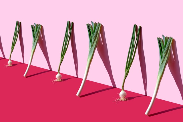green spring onions and leeks on the pink background