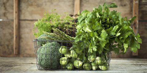 Verduras verdes y hierbas en cesta de alambre