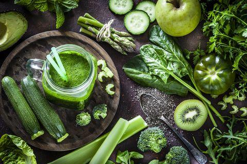 綠色蔬果與綠色蔬果汁擺在木頭桌上