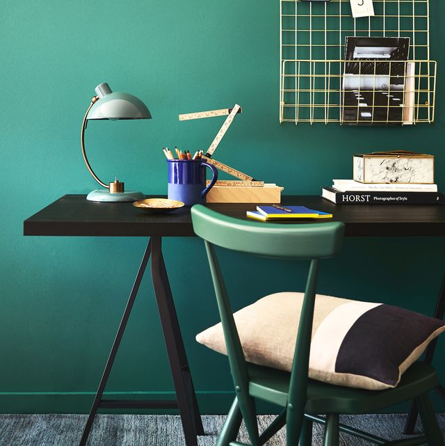 green teal walls behind a desk and a green chair, opulent office, rich teal forms a calming and stylish background to a practical workspace