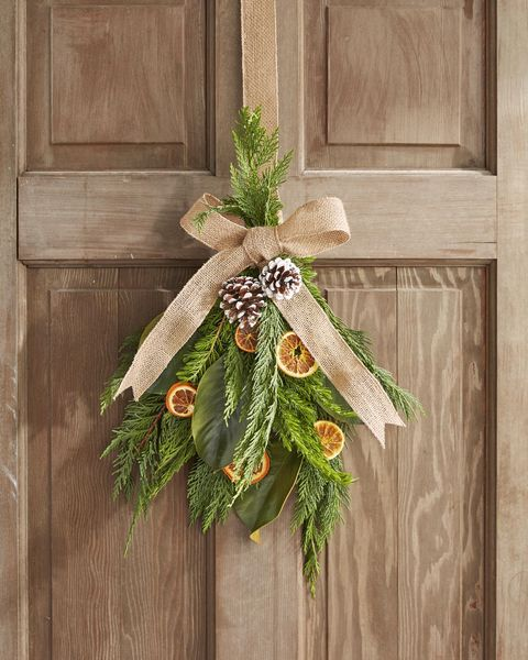 swag wreath made from greenery, dried fruit, and pine cones hung on a wood door and embellished with a burlap ribbon