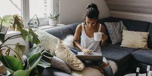 Vrouw op de bank op haar laptop