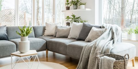 Grey corner couch with pillows and blankets in white living room interior  with windows and glass f3cf47186