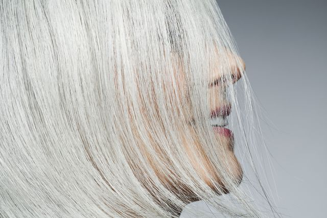 grey haired woman profile with hair covering face