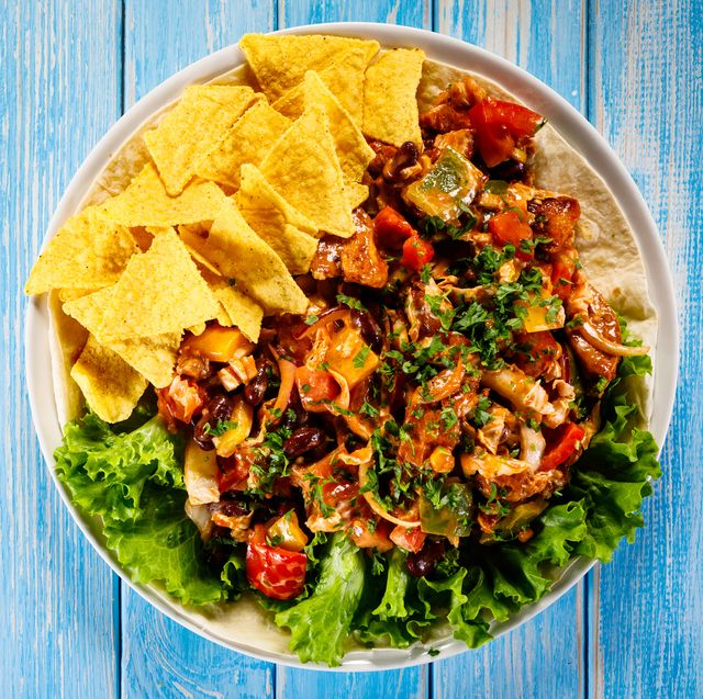grilled chicken meat, nachos and vegetables on wooden background