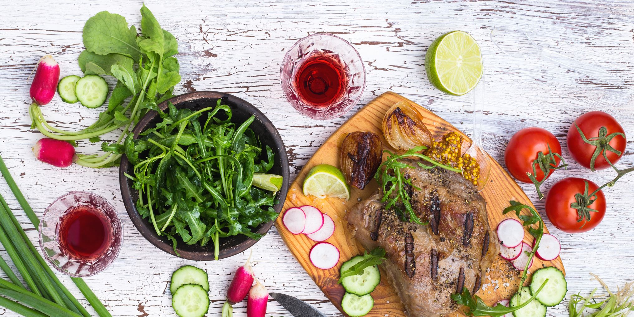 Grilled juicy meat with vegetables on a white rustic wooden background viewed from above, picnic table
