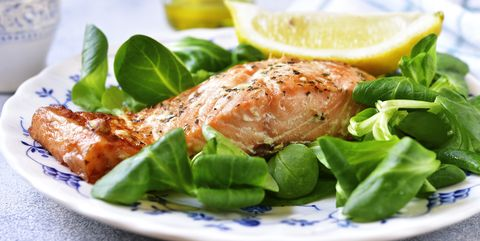 grilled organic salmon with salad leaves on a vintage plate