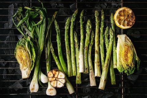 Grilled vegetables green asparagus, garlic, lemon, spring onion, salad on bbq grill rack over charcoal Top view, space