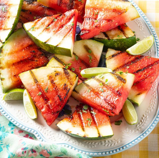 grilled watermelon with lime wedges on white platter