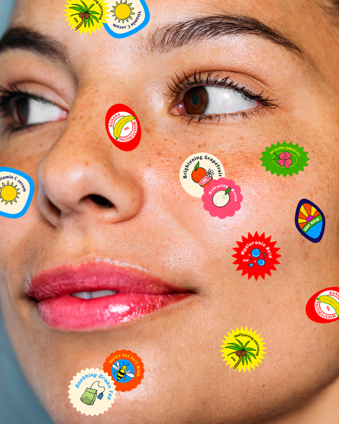 woman looking to the left with fruit stickers on her face