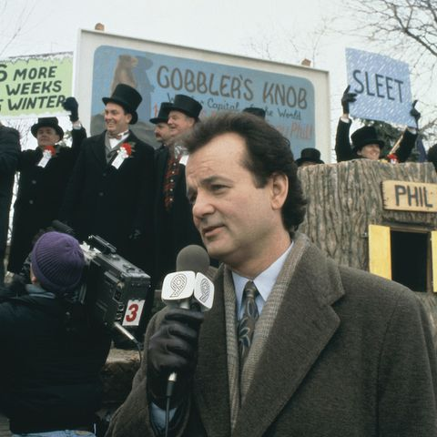 bill murray in groundhog day, holding a microphone
