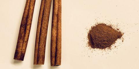 ground cinnamon and cinnamon sticks over white background