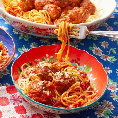 spaghetti and meatballs with fork twirling above