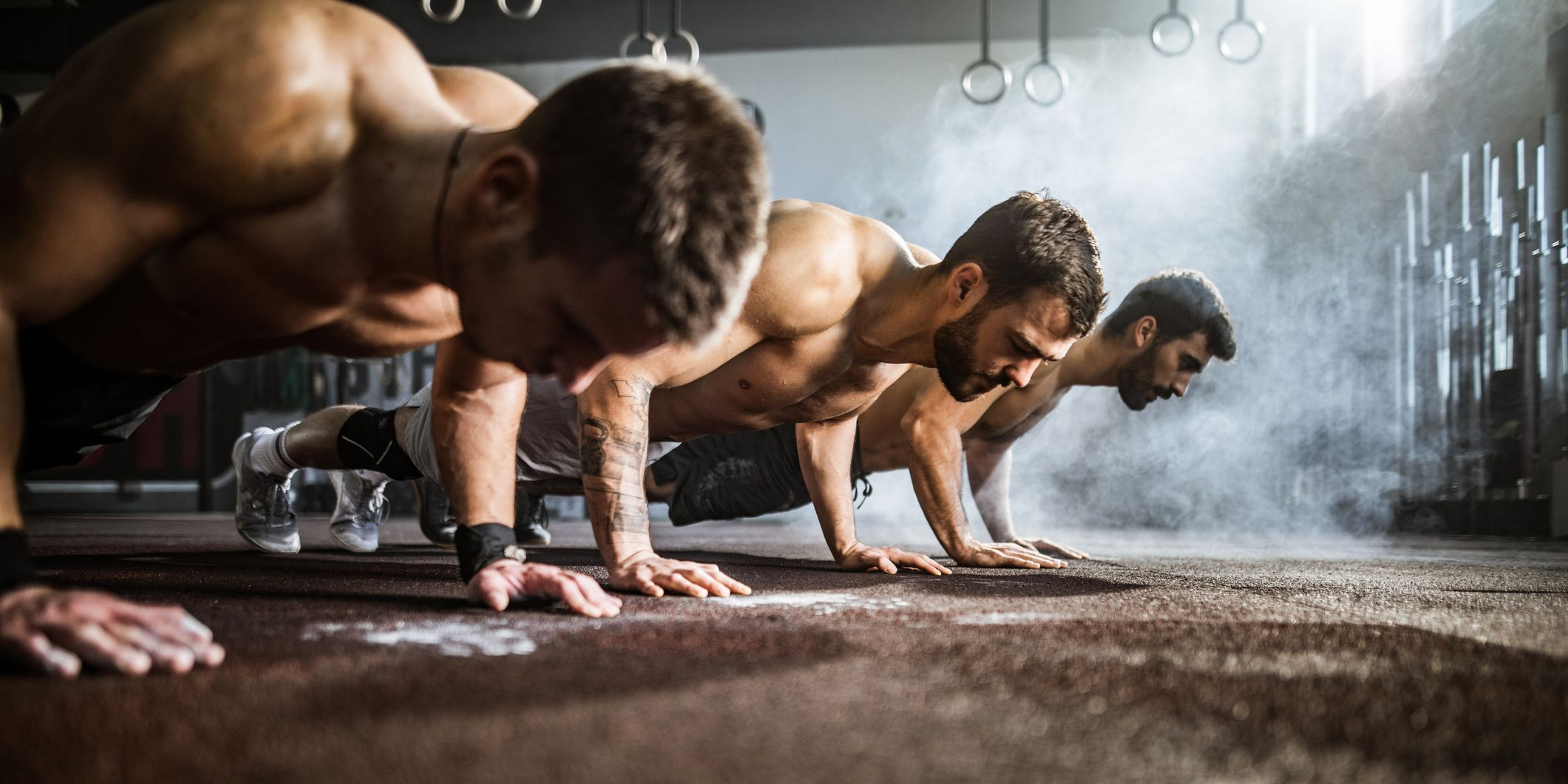 Group of athletic men exercising push-ups in a health club.