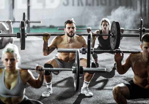 Group of athletic people exercising with barbells during cross training in a gym.