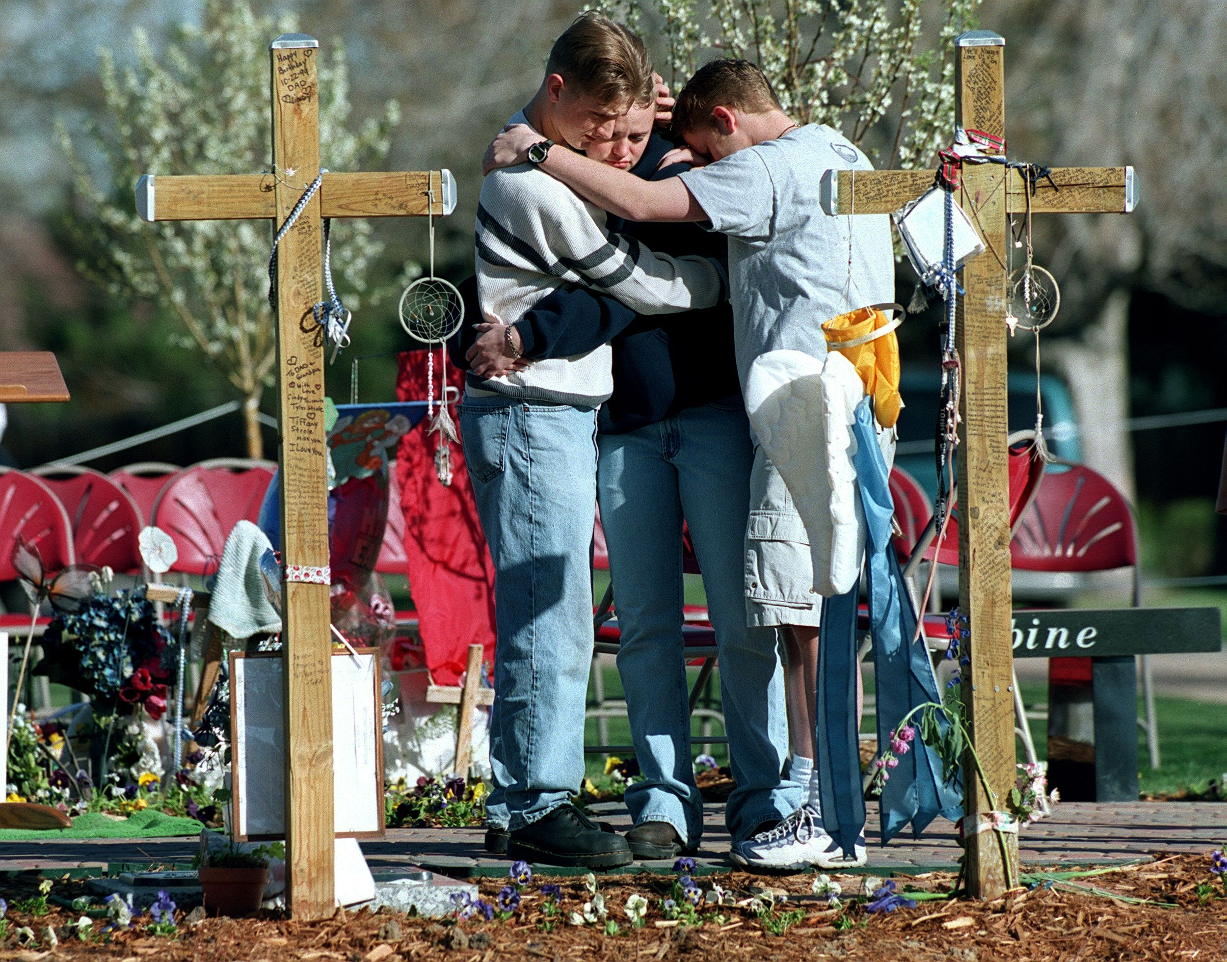 A group of Columbine students gather around crosses at Chapel Hill Memorial Gardens during the 11:21 am moment of silence on the one year anniversary of the Columbine High School Shootings.