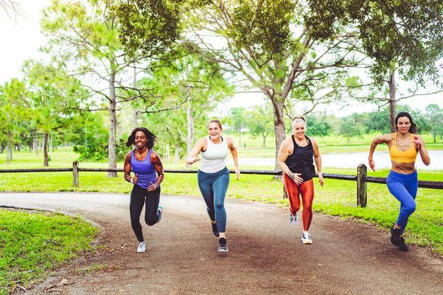 un grupo de mujeres esprintan en un parque durante una carrera