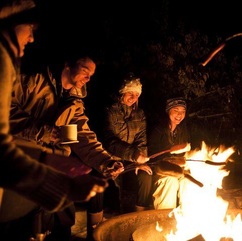Group of friend roasting hotdogs at night