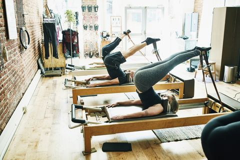 Group of mature pilates students using reformers during class in fitness studio