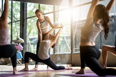 group of multi ethnics people learning yoga class in fitness club female caucasian instructor coaching and adjust correct pose to asian girl student at front while others doing follow them