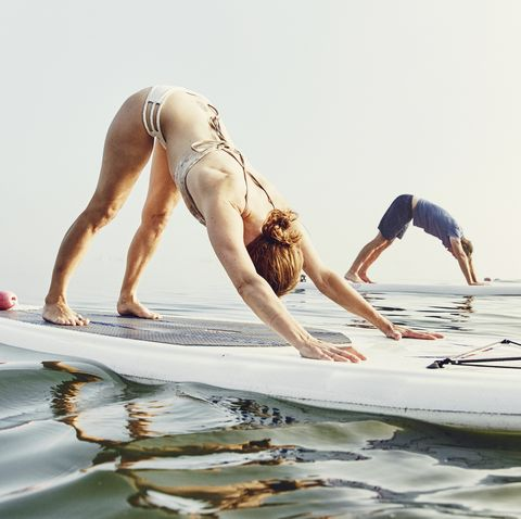 a group of standup paddle boarders doing yoga at sunrise in the fog