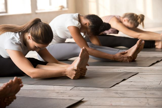 group of women practicing yoga lesson in paschimottanasana pose