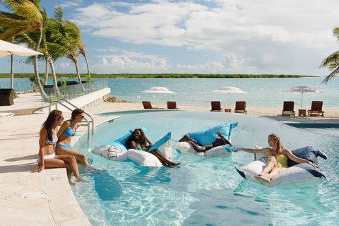 Group of young adults relaxing in swimming pool, Providenciales, Turks and Caicos Islands, Caribbean