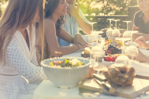 Grupo de amigos comiendo en verano.