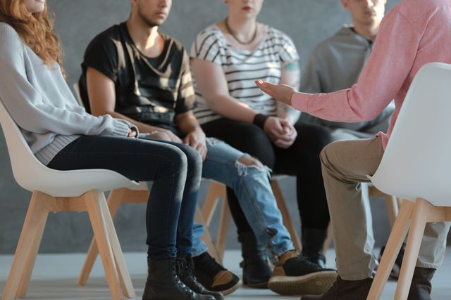 group of young people sitting in a circle and talking to psychiatrist  during a therapy