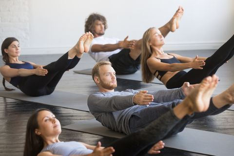 group of young sporty people in paripurna navasana pose