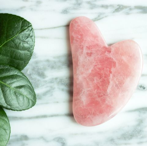a gua sha for the face and a flower against the marble background, view from above